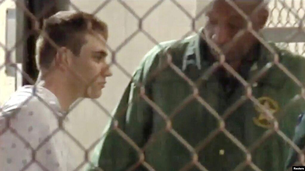 Una imagen tomada de video muestra a la policía acompañando a Nikolas Cruz en la cárcel del condado Broward luego de un tiroteo en la escuela secundaria Marjory Stoneman Douglas en Fort Lauderdale, Florida, el 15 de febrero de 2018.