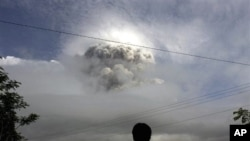 An Indonesian man watches as Mount Merapi erupts in Kepuharjo, Yogyakarta, 3 Nov. 2010.