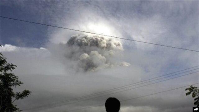 An Indonesian man watches as Mount Merapi erupts in Kepuharjo, Yogyakarta, 3 Nov. 2010.