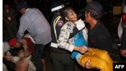 Камбоджійський поліцейський несе поранену особу