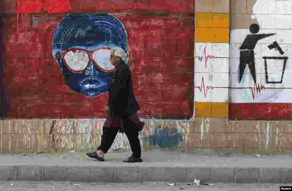 A man walks past a wall adorned with graffiti painted by various artists to promote peace, along a sidewalk in Karachi, Pakistan.