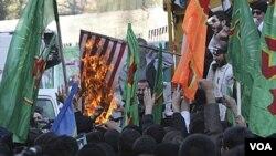 Peserta demo di depan bekas Kedubes AS di Teheran membakar bendera Amerika, Jumat (4/11) dalam aksi protes tahunan memperingati pendudukan Kedubes AS di tahun 1979.