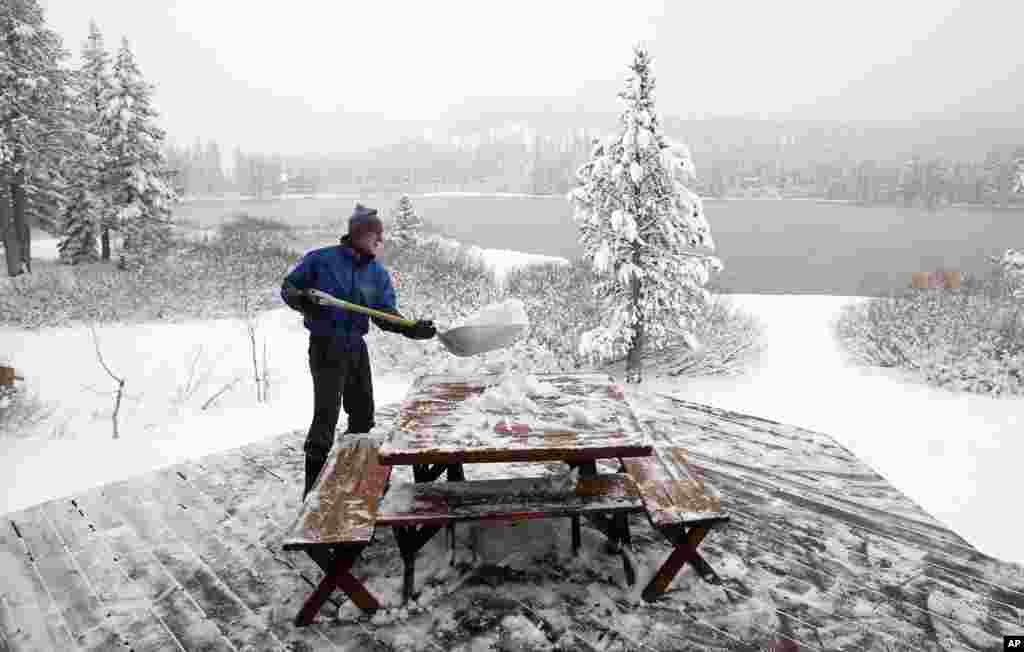 Mickey Gray cleans snow from the deck of his home overlooking Serene Lakes near Soda Springs, California, Oct. 28, 2013. As much as 10 inches of snow fell in the Sierra Nevada near Donner Summit overnight.