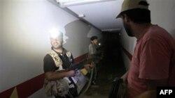 Повстанцы обследуют тоннель в бункере под резиденцией Муаммара Каддафи в Триполи. 25 августа 2011 года