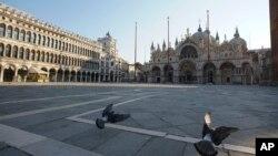 Burung merpati di lapang Santo Markus yang lengang di Venesia, Italia setelah penerapan aturan tinggal di rumah untuk mencegah penularan Covid-19, 6 April 2020.