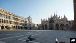 Pidgeons fly in deserted St. Mark's Square, in Venice, Monday, April 6, 2020.
