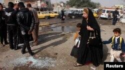 一位母親帶了子女2月9日在巴格達社區行經一處被自殺炸彈爆炸襲擊過的街道。