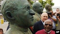 L'ancien lauréat du prix Nobel, Desmond Tutu, avant-plan, et l'ancien président sud-africain FW de Klerk, arrière-plan, regardent des statues faites à leur visage lors d'une cérémonie de dévoilement au Cap, Afrique du Sud, 16 décembre 2005.