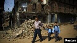尼泊爾巴克塔布的一位父親路經倒塌的房屋送他的兩個兒子去上學(2015年5月31日)