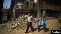 Birendra Karmacharya (L) walks past the debris of collapsed houses while holding the hand of his younger son Saksham Karmacharya, 4, along with his elder son Biyon Karmacharya (R), 9, as they head towards the school in Bhaktapur, Nepal, May 31, 2015.