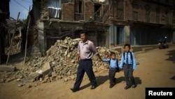 Birendra Karmacharya (kiri) berjalan melewati puing-puing rumah sambil menggandeng anaknya Saksham Karmacharya, 4, dan Biyon Karmacharya (kanan), 9, menuju sekolah di Bhaktapur, Nepal, 31 Mei 2015.