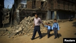 尼泊尔巴克塔布的一位父亲路经倒塌的房屋送他的两个儿子去上学(2015年5月31日)