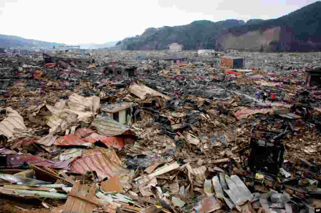 Residents walk past debris in an area hit by an earthquake and tsunami in Otsuchi March 15, 2011. In the town of Otsuchi in Iwate prefecture, 12,000 out of a population of 15,000 have disappeared following Friday's massive earthquake and tsunami. REUTERS/
