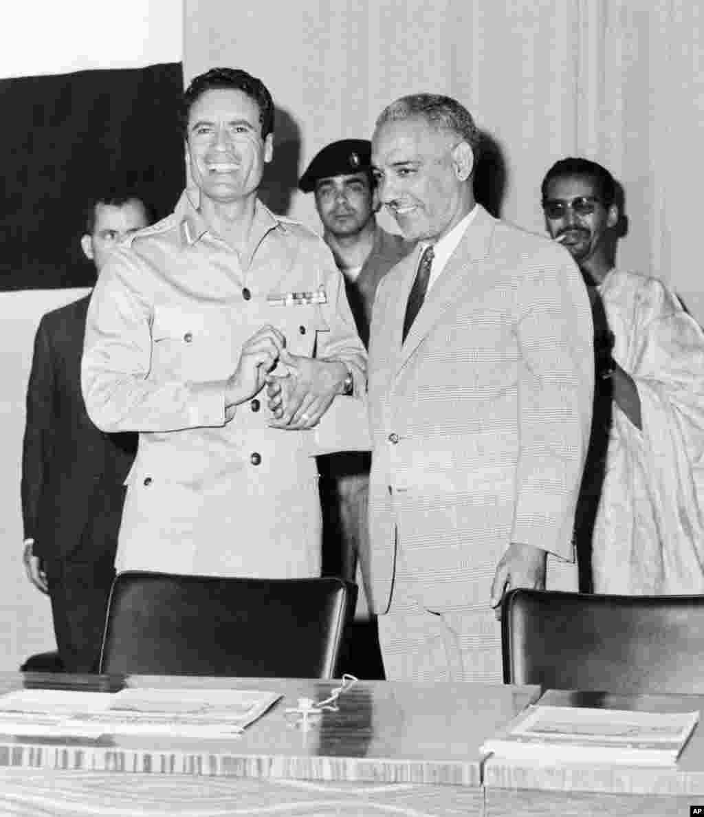 这张照片摄于1969年,是利比亚国家元首卡扎菲(左)在的黎波里与毛里塔尼亚总统达达握手的情形。(法新社)