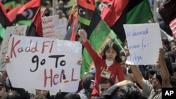 A young girl waves the opposition flag as an angry but peaceful crowd demonstrates outside the Tibesty Hotel where an African Union delegation was meeting with opposition leaders in Benghazi, Libya, April 11, 2011