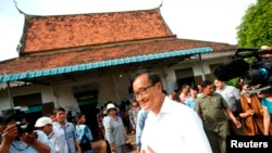 Sam Rainsy, president of the Cambodia National Rescue Party (CNRP), visits a polling station during the general elections at a pagoda in Phnom Penh July 28, 2013.