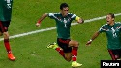 Le Mexicain Rafael Marquez, au centre, célèbre ses coéquipiers Paul Aguilar et Javier Hernandez après avoir marqué le premier but de son équipe contre la Croatie à l'arène de Pernambuo à Recife le 23 juin 2014.c
