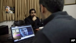 "Farhad Azima, Iranian director and screenwriter of the animated film ""Battle of the Persian Gulf II"" (center) gives an interview, while a man watches a trailer for the movie, at his office, in Tehran, Iran, Feb. 26, 2017."