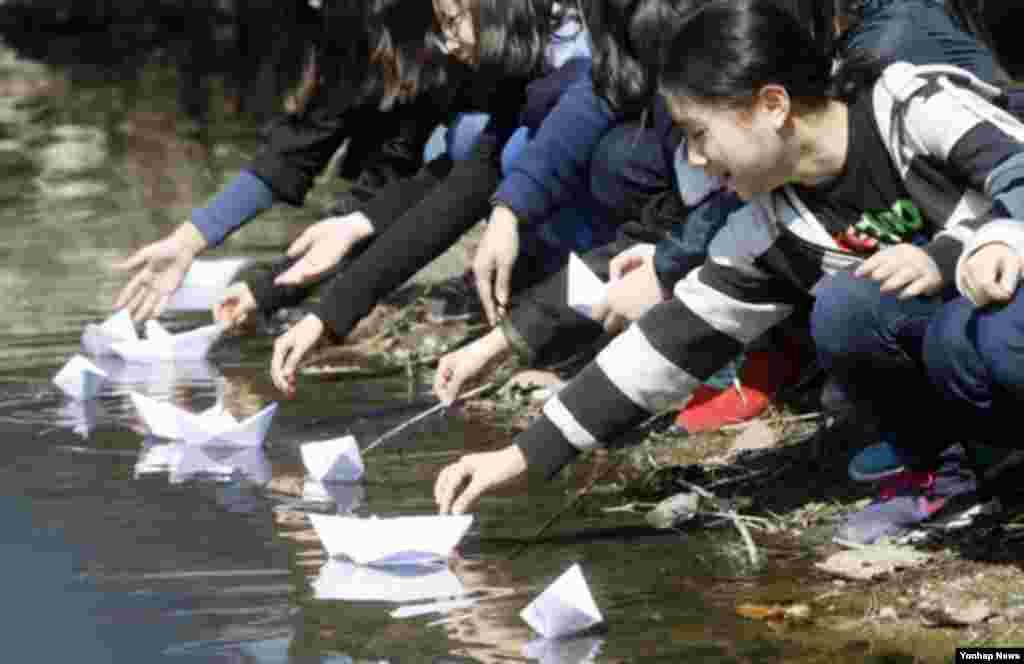 26일 한국 춘천시 이디오피아한국전참전기념관 앞에서 열린 '천안함 피격 사건 3주기 추모식'에서 신남초등학교 학생들이 직접 쓴 추모 편지를 종이배로 접어 공지천에 띄워 보내고 있다.