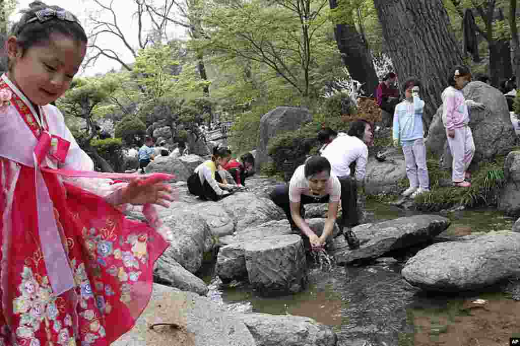 Người Triều Tiên nhúng tay vào một dòng suối tại Bình Nhưỡng, Bắc Triều Tiên vào Ngày Lễ Lao động, ngày 1 tháng 5, 2012. Các gia đình Bắc Triều Tiên đôå xô đến các công viên, sân chơi và các quảng trường để vui hưởng Ngày Lễ Lao động với những cuộc cắm tr