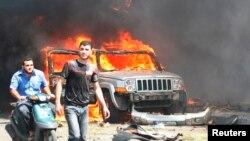 Civili prolaze pored zapaljenih automobila u napadima u Tripoliju, u Libanu