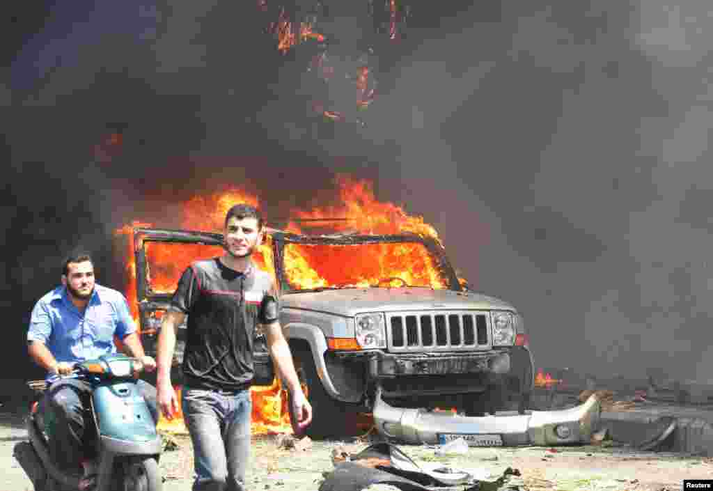 Civilians are seen near a burning car outside one of two mosques hit by explosions, Tripoli, Lebanon, August 23, 2013.