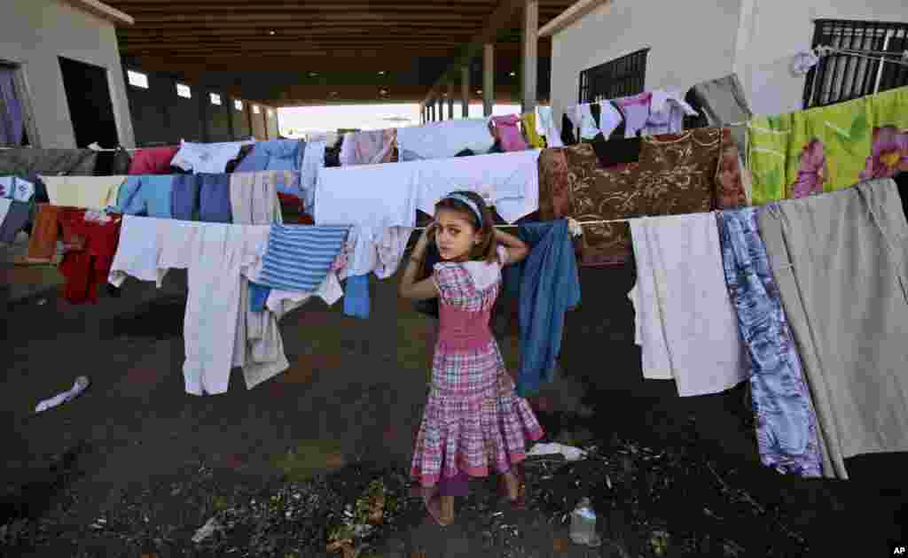 A Syrian girl, who fled her home with her family due to fighting between the Syrian army and the rebels, looks back while checking her laundry, near the Syrian town of Azaz, Aug. 26, 2012.