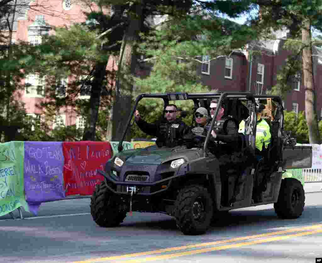 A State Police Special Response team patrols past posters of encouragement at Wellesley College before the start of the 118th Boston Marathon, Wellesley, Mass., April 21, 2014.