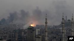 Bola api terlihat di kawasan timur Aleppo, Suriah, menyusul serangan udara yang menghantam wilayah itu (5/12). (AP/Hassan Ammar)