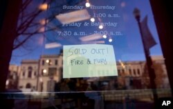 "A sign posted at the door for Kramerbooks & Afterwords Cafe shows that the book ""Fire and Fury: Inside the Trump White House"" is sold out at the bookstore located in the Dupont Circle neighborhood in Washington, Friday, Jan. 5, 2018. (AP Photo)"