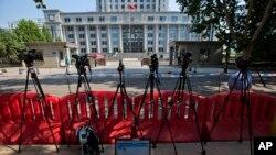 济南中级法院外面,一位记者观看关于庭审薄熙来的微博