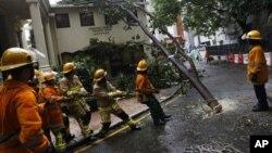 Para petugas membersihkan jalanan dari pohon tumbang akibat terpaan topan Vicente di Hong Kong (24/7).