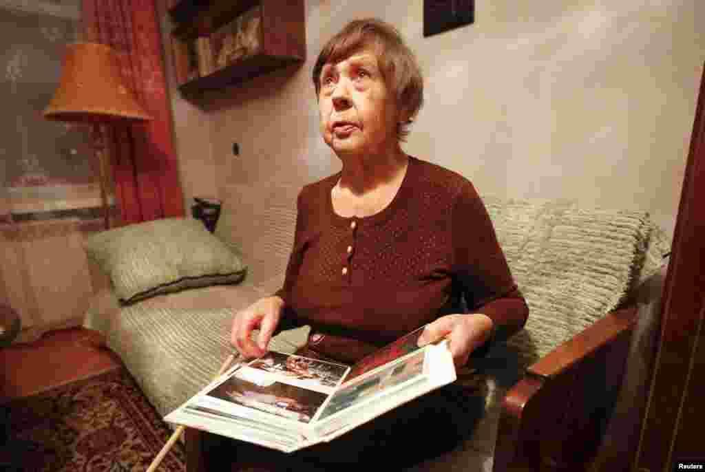 Varvara Tolokonnikova, grandmother of Nadezhda Tolokonnikova, shows family photos of Nadezhda at her apartment, as she waited for her granddaughter's release from prison, Dec. 21, 2013.