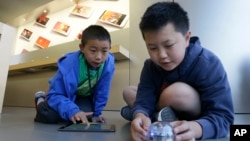 Apple Camp students Brandon Wong, 9, left, and Matthew Choy, 12, learn to program robots using the Sphero SPRK+ with the Lightning Lab application during a Coding Games and Programming Robots session in San Francisco, Wednesday, July 27, 2016. (AP Photo/J