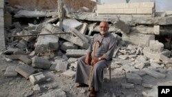 요르단 서안지구에서 이스라엘 소년 납치용의자들의 집이 이스라엘 군에 의해 철거된 가운데, 18일 한 팔레스타인 노인이 건물 잔해 주변에 앉아있다.