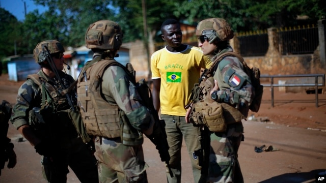 FILE - French Sangaris peacekeepers are seen speaking to a local resident outside Fatima Church in Bangui, Central African Republic.