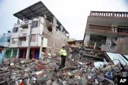 Cảnh sát đứng trên đống đổ nát bên cạnh những tòa nhà bị phá hủy vì trận động đất ở thành phố Pedernales, Ecuador, ngày 17 tháng 4, 2016.