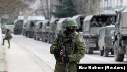 Prajurit bersenjata menunggu di kendaraan tentara Rusia di luar pos penjaga perbatasan Ukraina di Kota Krimea Balaclava, 1 Maret 2014. (Foto: REUTERS/Baz Ratner)
