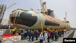 Employees stand near the Indian Navy's first Scorpene submarine before being undocked on April 6 at a naval vessel ship building yard in Mumbai.