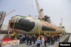 Employees stand near the Indian Navy's first Scorpene submarine before being undocked at a naval vessel ship building yard, in Mumbai.
