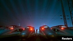 FILE - A worker stands among CRH (China Railway High-speed) Harmony bullet trains at a high-speed train maintenance base in Wuhan, Hubei province, March 9, 2015.