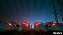 在湖北武汉的高速列车维修基地,一名工人站在和谐号高速列车中间。(2015年5月9日资料照)