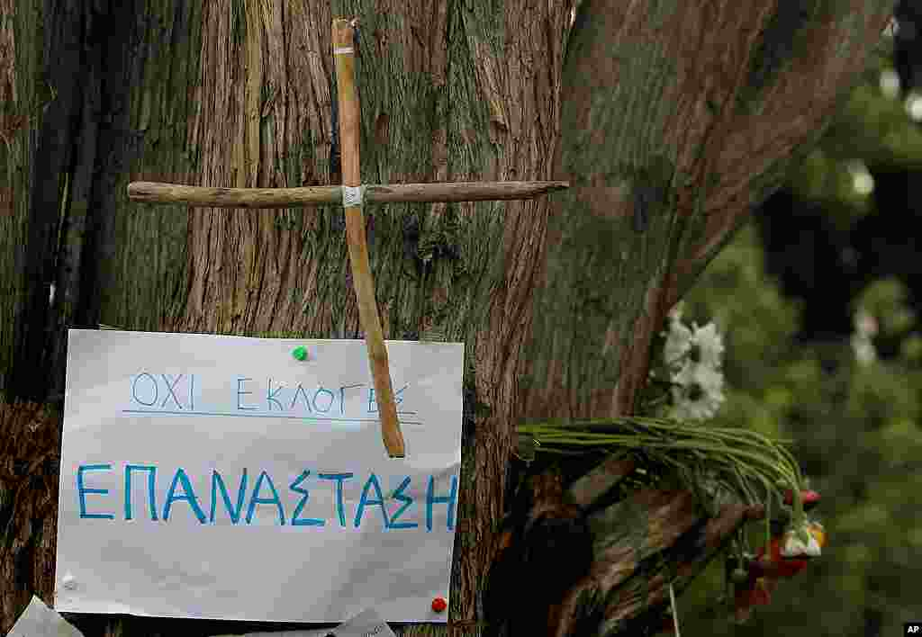 A note and a wooden cross pinned on the trunk of a tree under which an elderly man fatally shot himself at Athens' main Syntagma square, Athens, Greece, April 5, 2012.(AP)