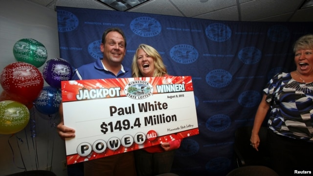 Paul White, from Ham Lake, Minnesota, stands with his partner Kim VanReese as he holds a check for his $149.4 million portion of a $448.4 million Powerball jackpot prize.
