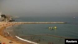 Des gens profitent de la plage alors que la police patrouillent, dans le détroit de Gibraltar, le 10 août 2015.