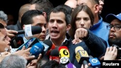 Venezuelan opposition leader and self-proclaimed interim president Juan Guaido accompanied by his wife Fabiana Rosales, speaks to the media in Caracas, Jan. 27, 2019.