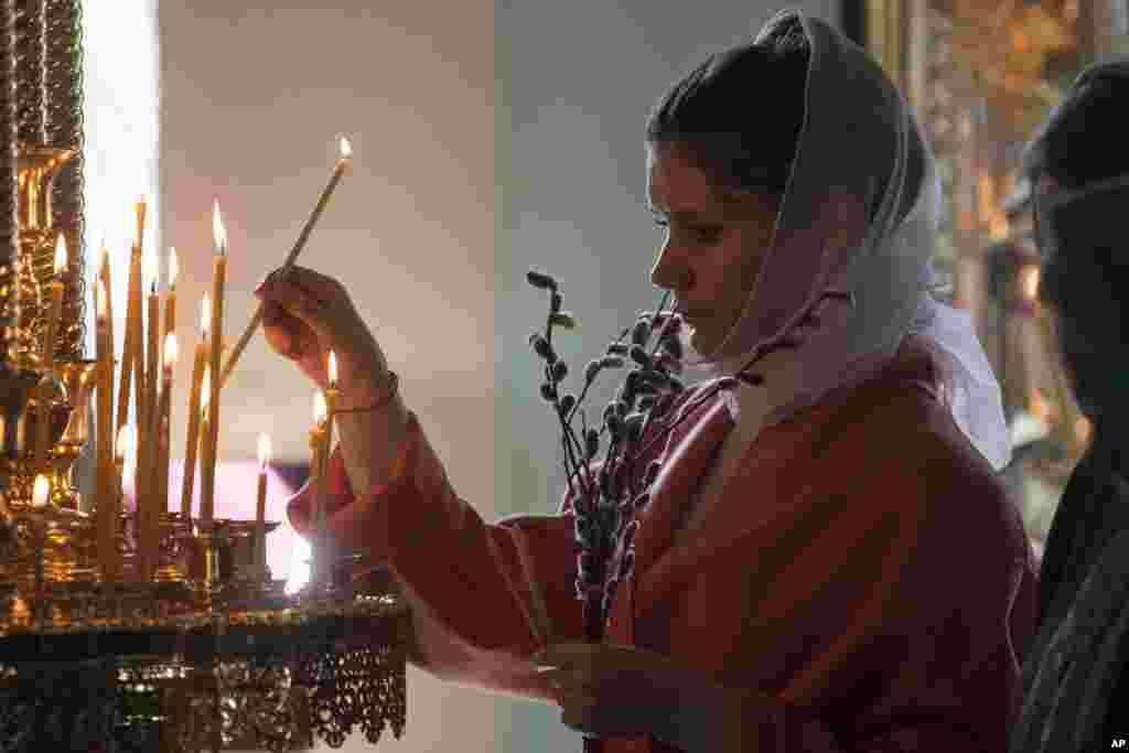 A woman lights a candle during the Palm Sunday Mass inside the St. Peter's Cathedral in the High-Petrovsky monastery in Moscow, Russia.