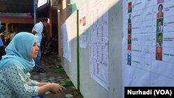 Seorang pemilih memeriksa daftar legislatif yang dipasang di sebuah TPS di Sleman, DIY dalam Pemilu 2019. (Foto:VOA/Nurhadi)