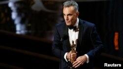 """Daniel Day Lewis menerima penghargaan sebagai aktor terbaik untuk perannya dalam """"Lincoln"""" dalam Academy Awards ke-85 di Los Angeles (24/2). (Reuters/Mario Anzuoni)"""