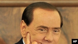 Italian Prime Minister Silvio Berlusconi looks on as he attend a meeting with Confcommercio in Milan, February 28, 2011